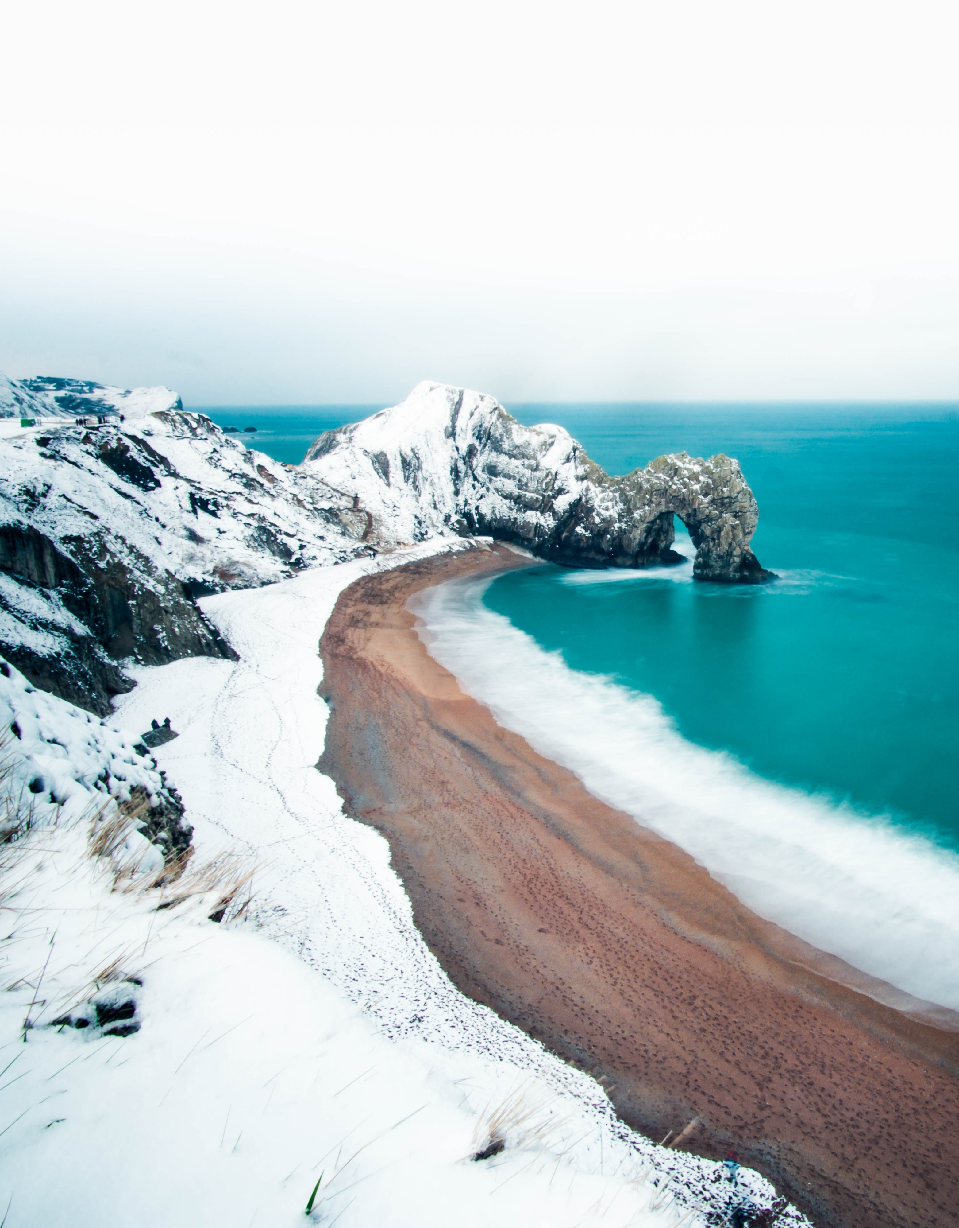 rock formation mountain covered by snow near sea