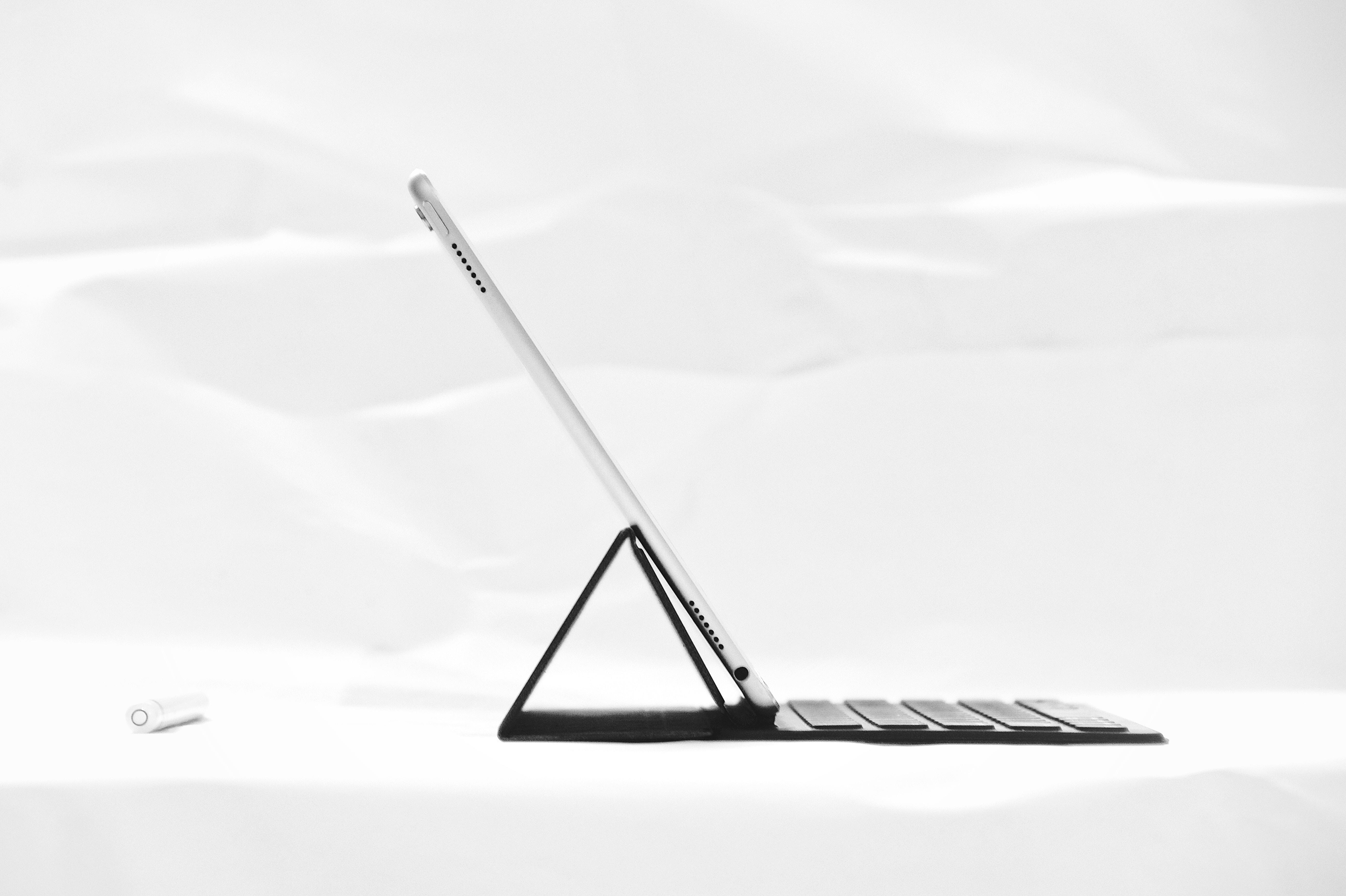 silver iPad on black dock keyboard