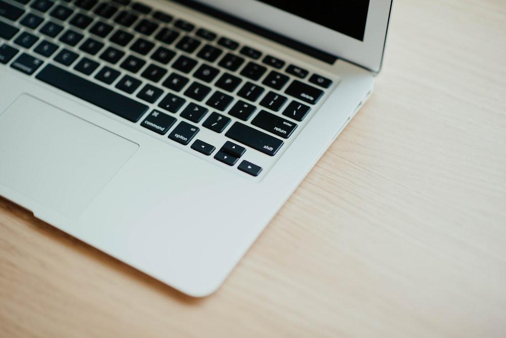 MacBook Air on top of brown wooden furniture