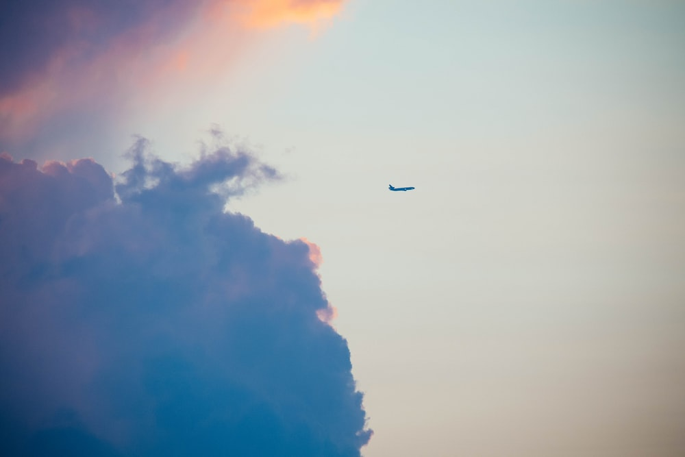 plane on the sky and nimbus clouds