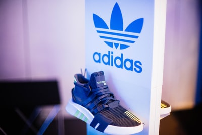 shallow focus photography of unpaired gray adidas sports shoe sneaker zoom background