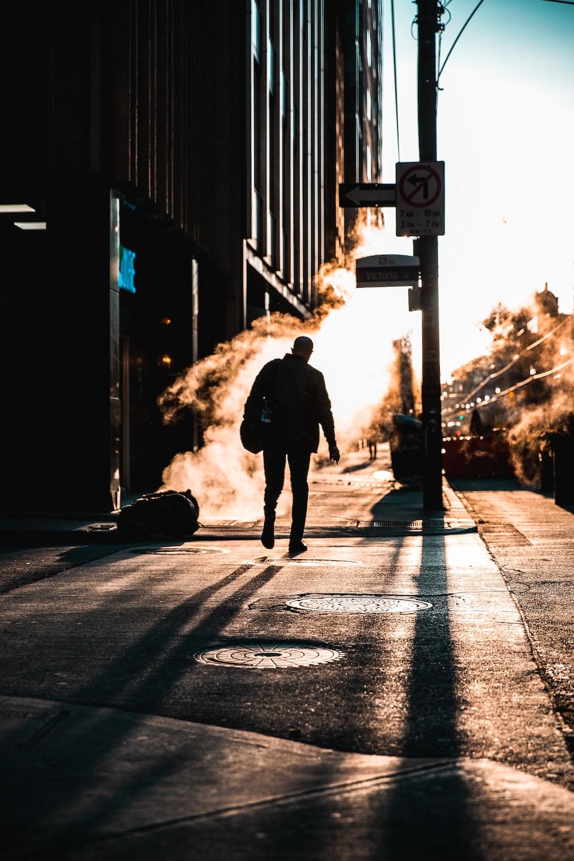 man in black jacket walking on the road