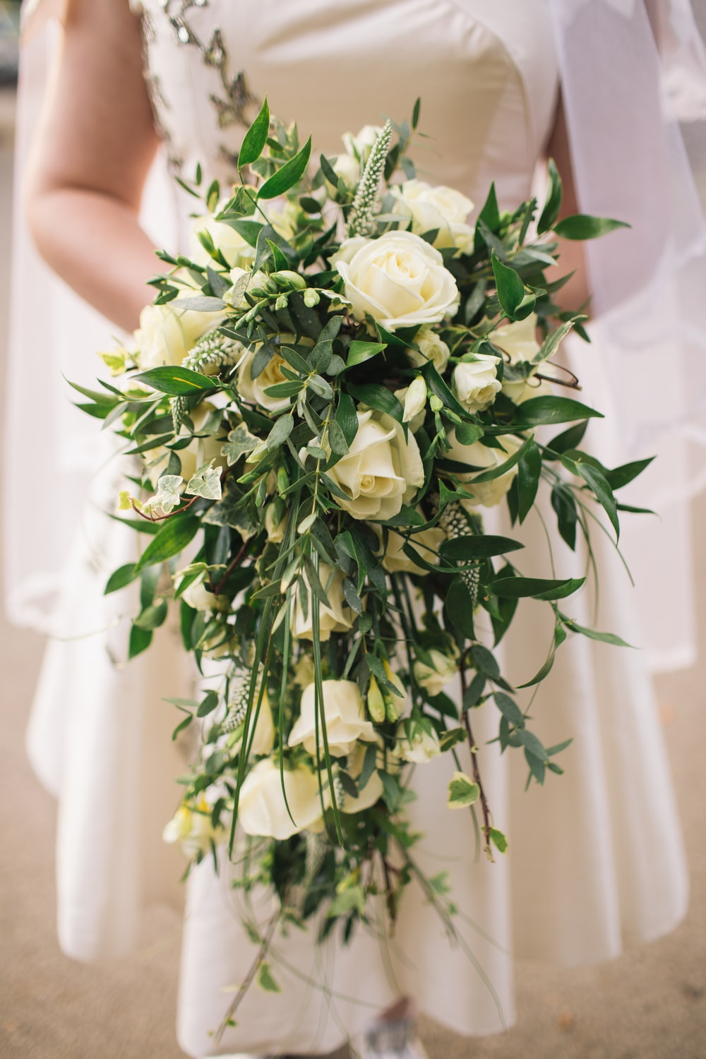 woman holding white roses bouquet