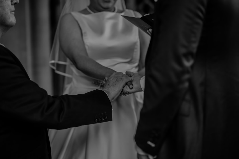 grayscale photo of bride and groom holding hands