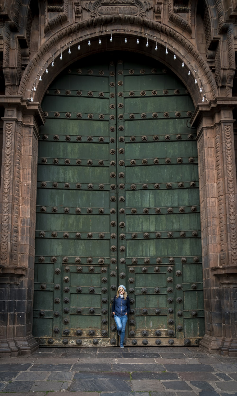 woman leaning on large green door