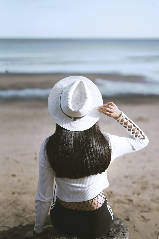 woman sits on rock watching ocean