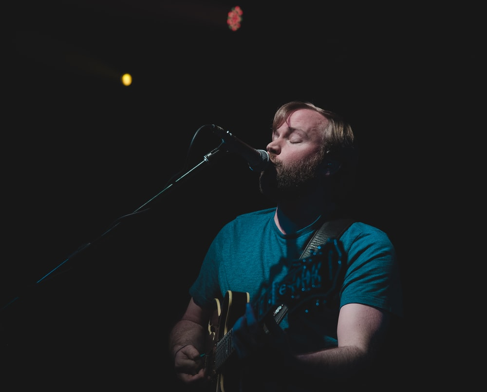 man singing while playing guitar