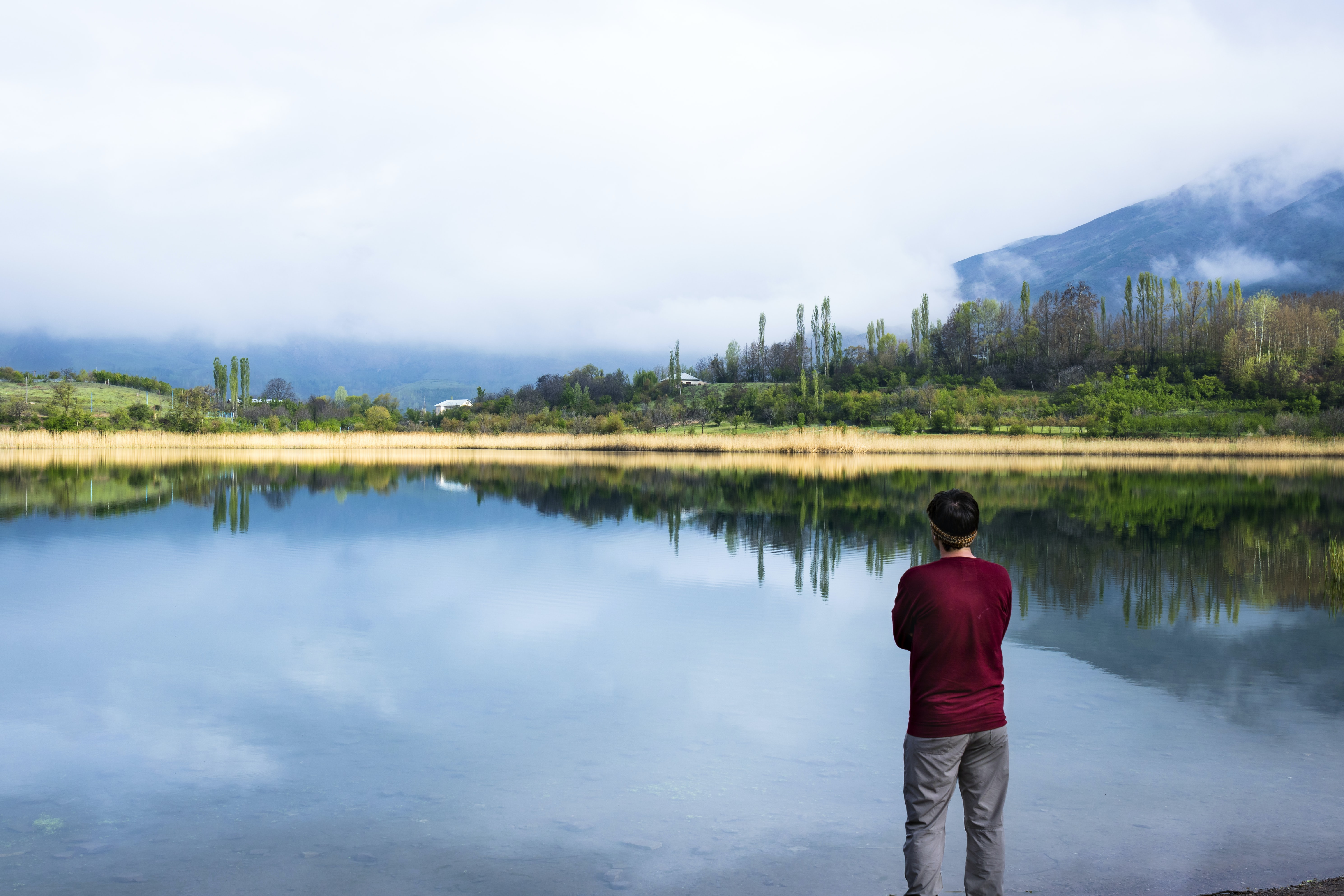 man standing near body of water and trees