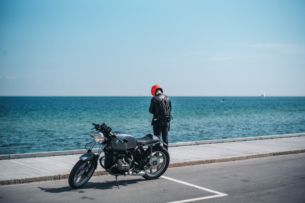 person standing beside motorcycle near body of water
