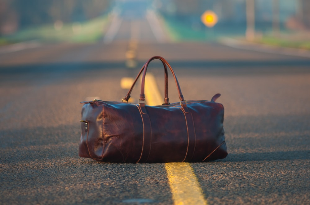 brown leather duffel bag in middle on gray asphalt road