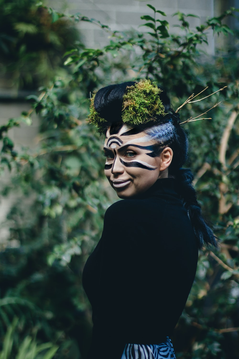 woman wearing black turtleneck top with face paint and headdress