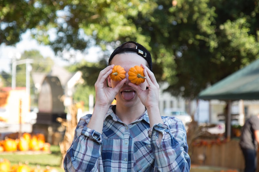 A young man holds two small pumpkins in front of his eyes and sticks his tongue out.