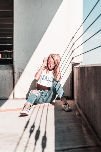 woman sitting on floor wearing white crop top