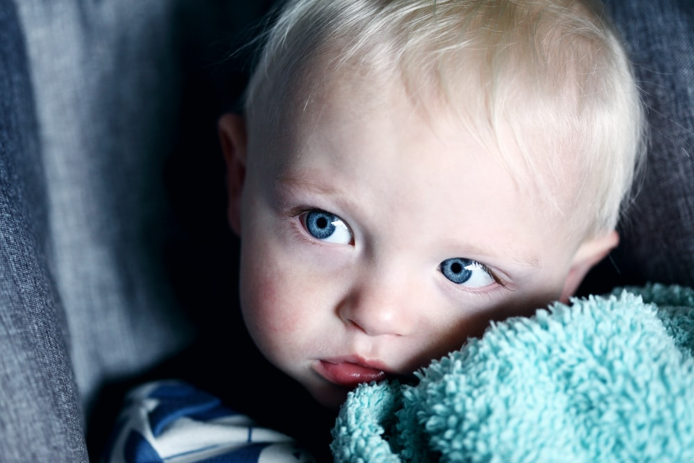 baby beside green textile