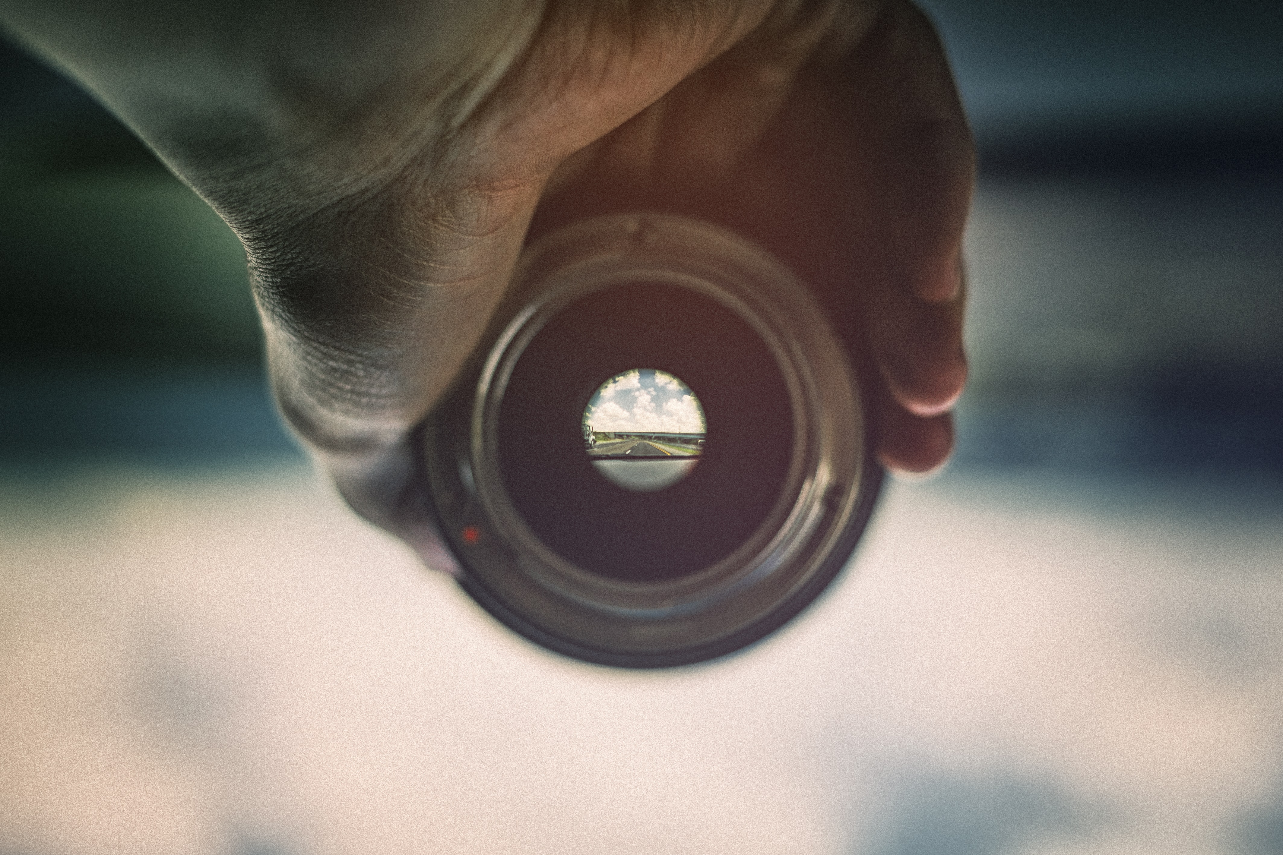 person holding camera lens viewing mountains