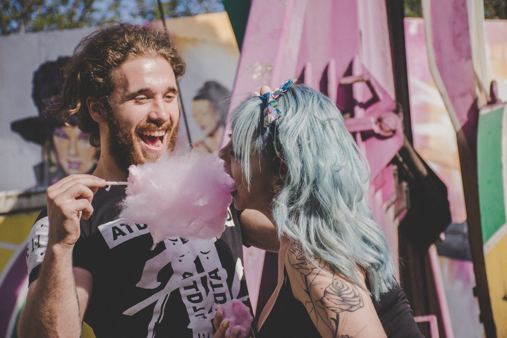 man and woman laughing while eating cotton candy