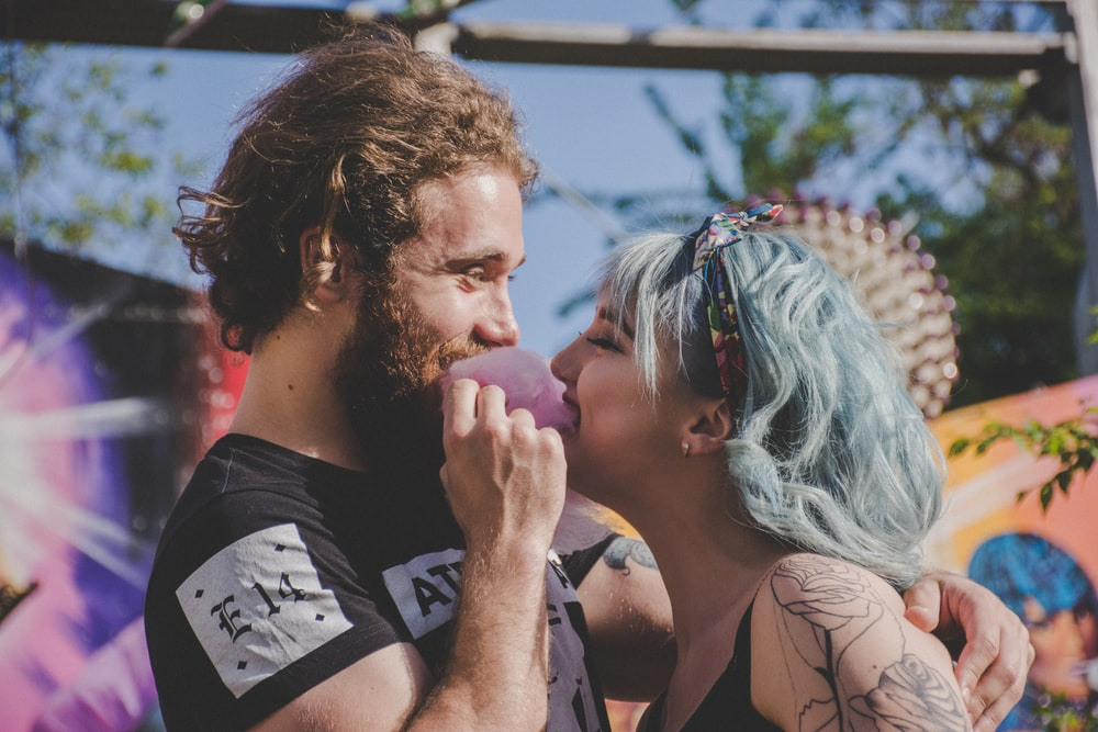man and woman biting cotton candy