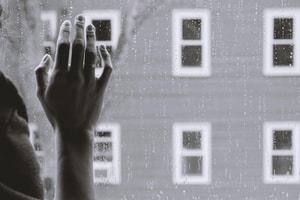 grayscale photo of woman right hand on glass