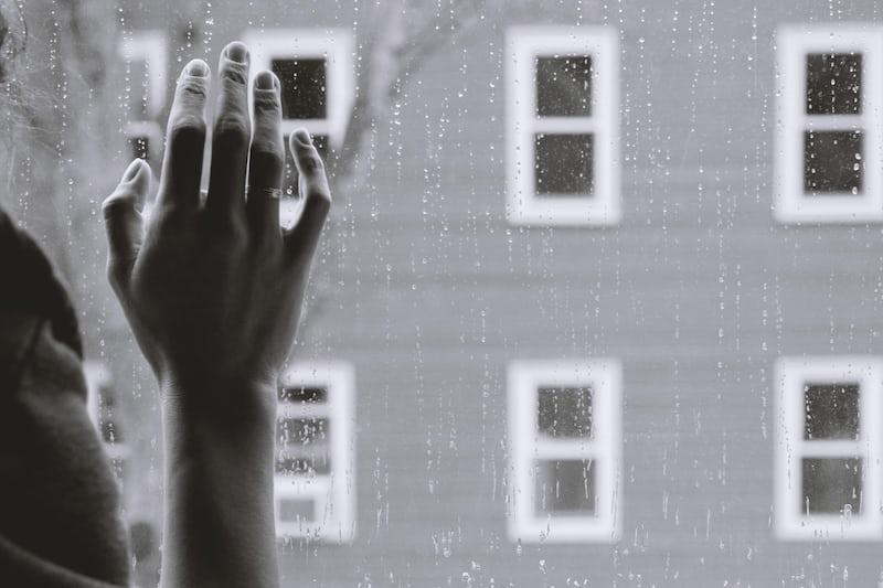窓に手を当てる人