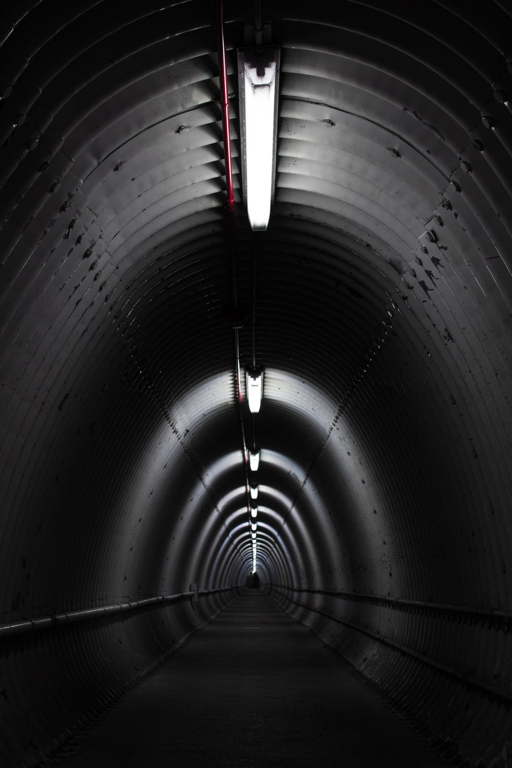gray concrete tunnel with light