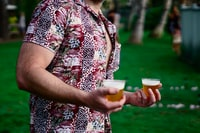 man holding filled beer cups