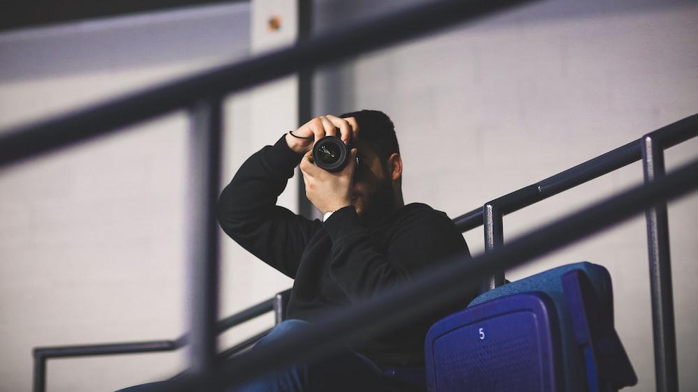 man sitting and taking photo at daytime