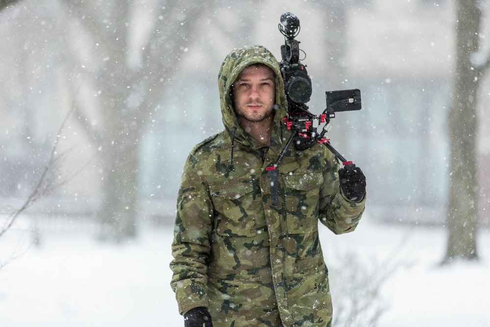 man in green and black camouflage hooded jacket holding black professional camera