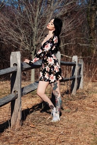 woman in white, black, and red floral dress holding on brown wooden fence