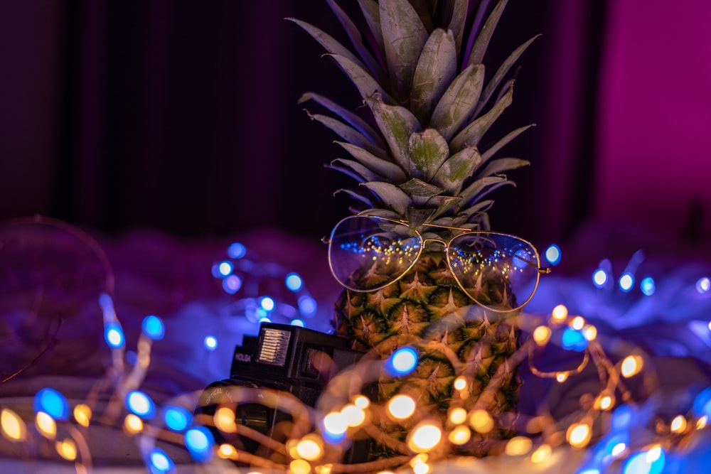 eyeglasses on pineapple surrounded with string light