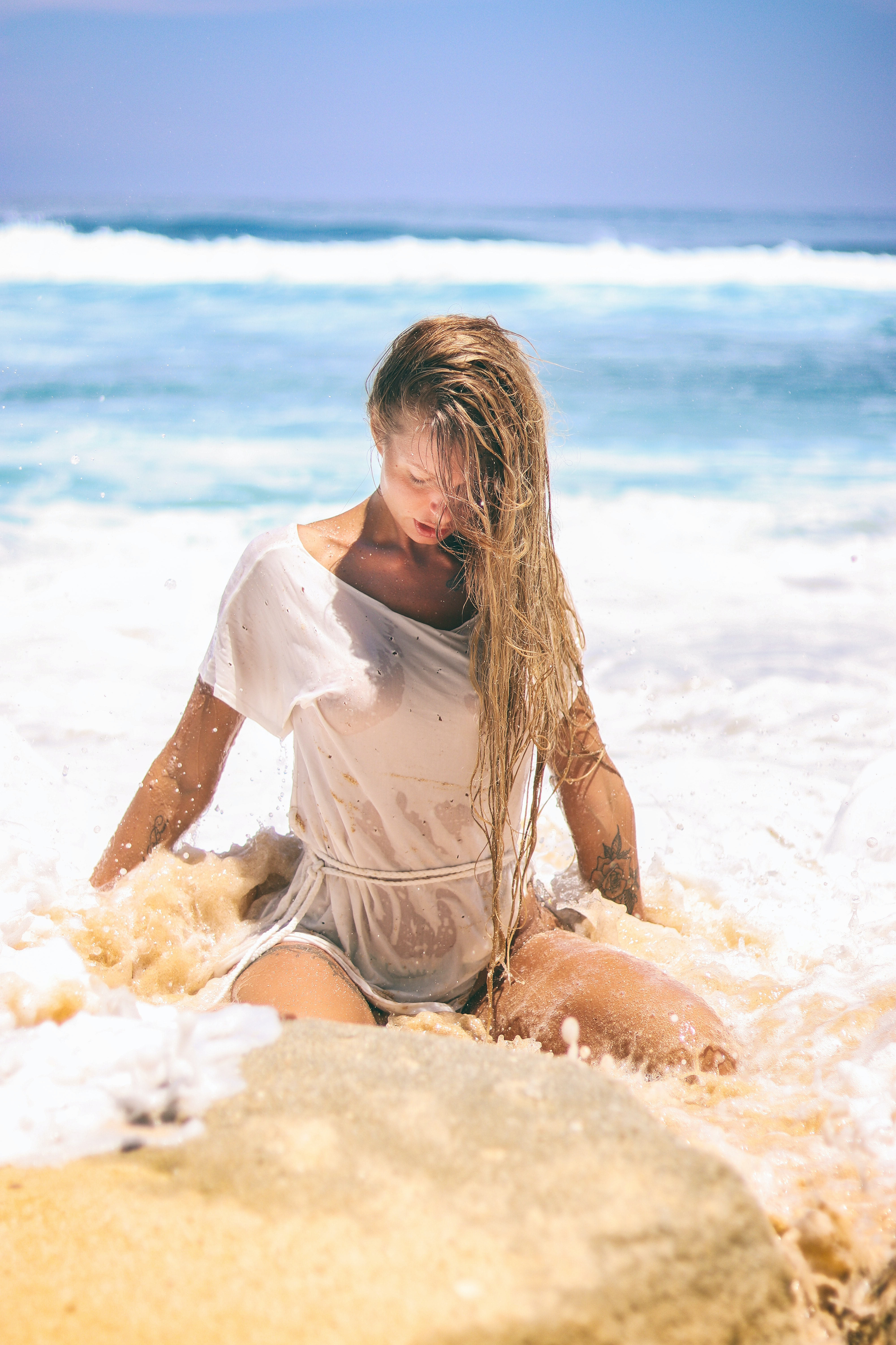 woman in white top sitting on sand near body of water