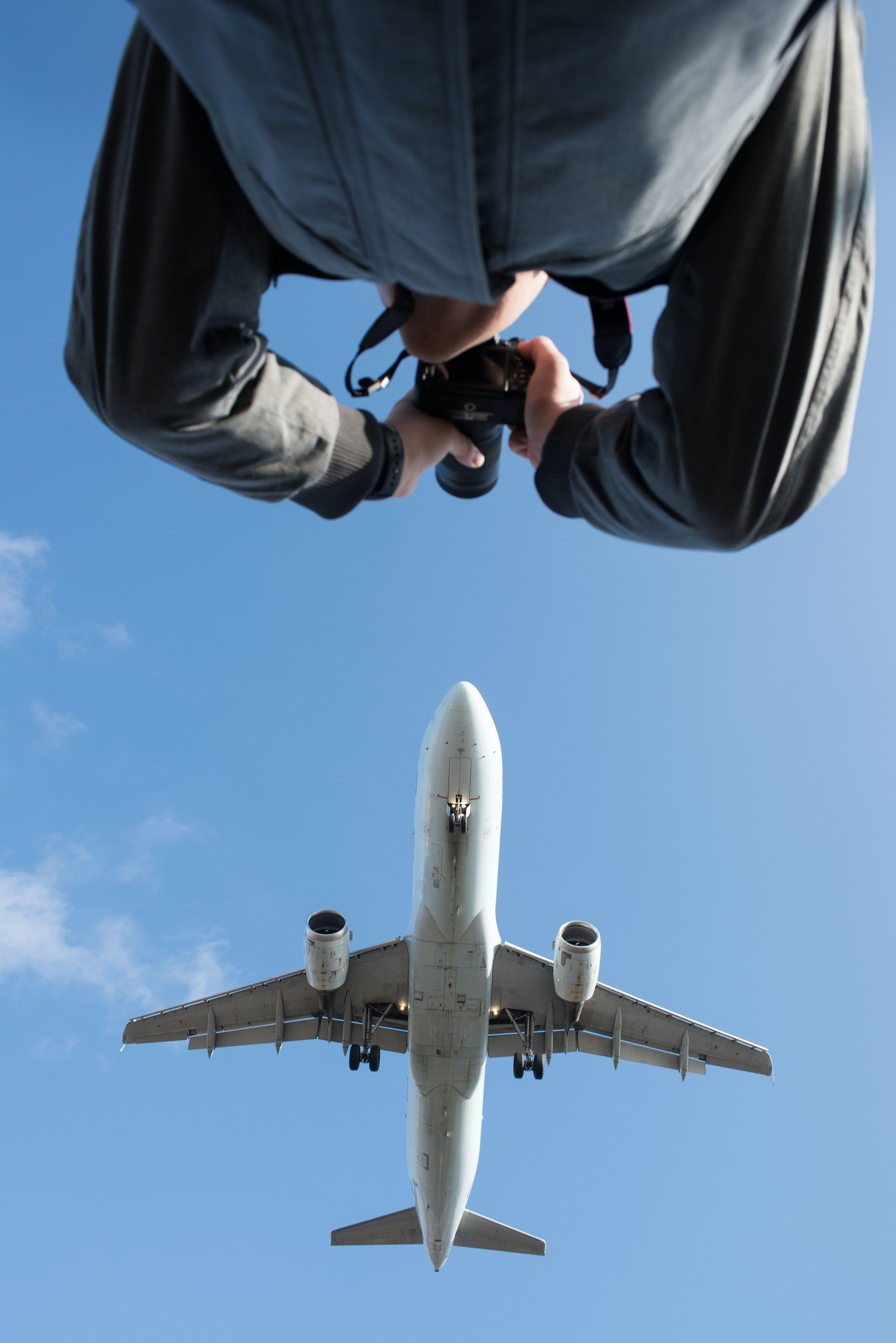 low angle photography of man taking photo of plane during daytime