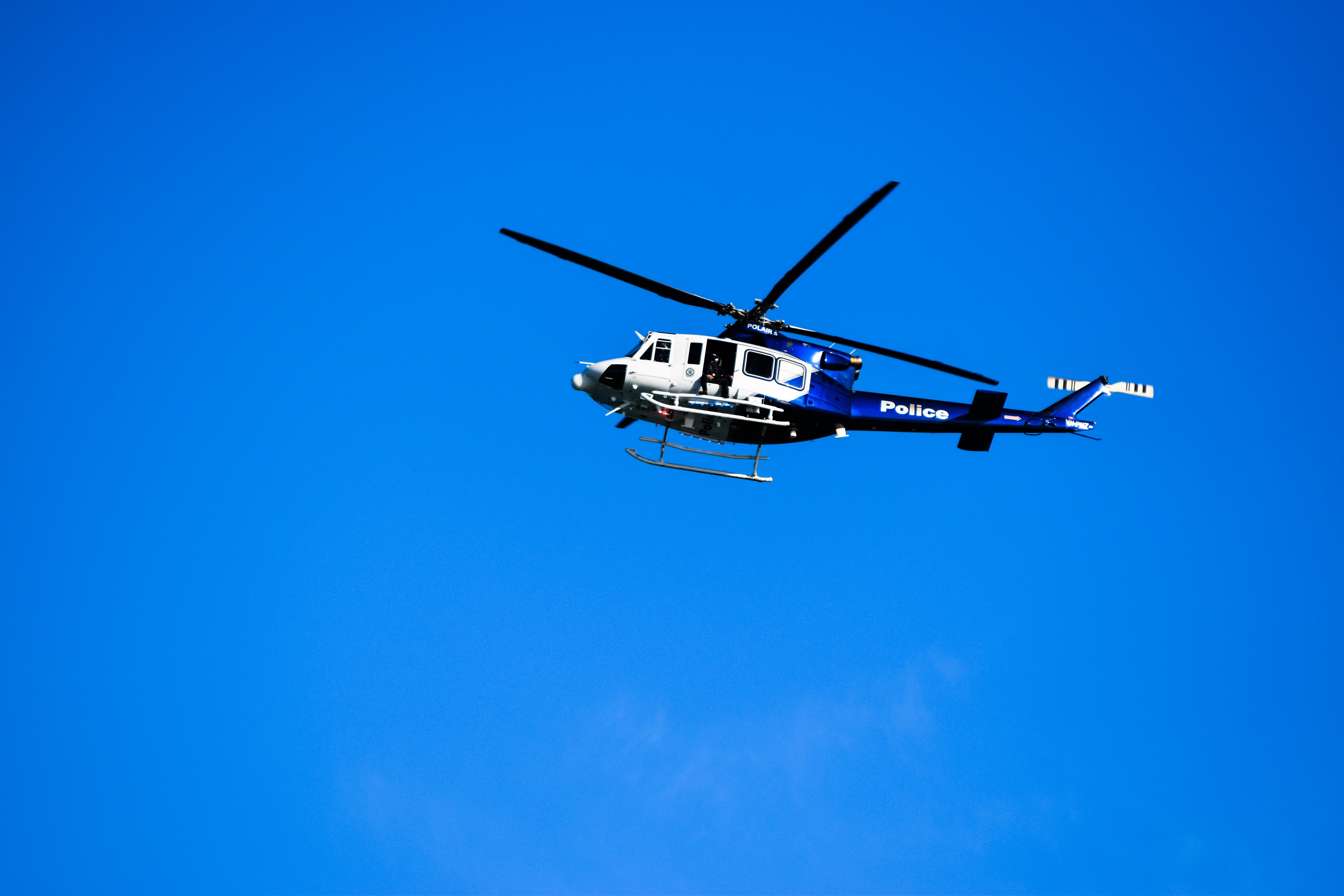 white and blue Police chopper flying in the sky