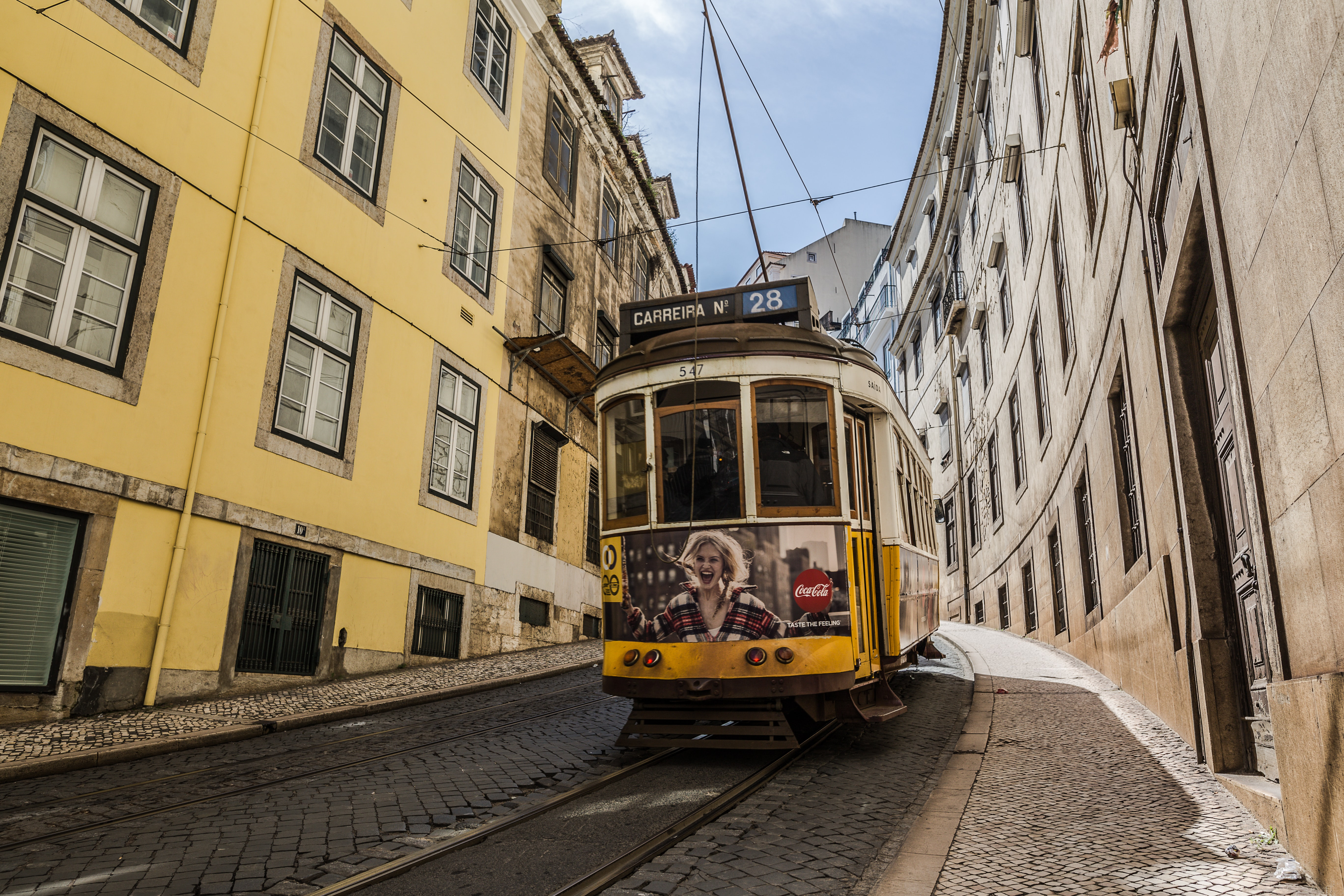 yellow tram car in between buildings