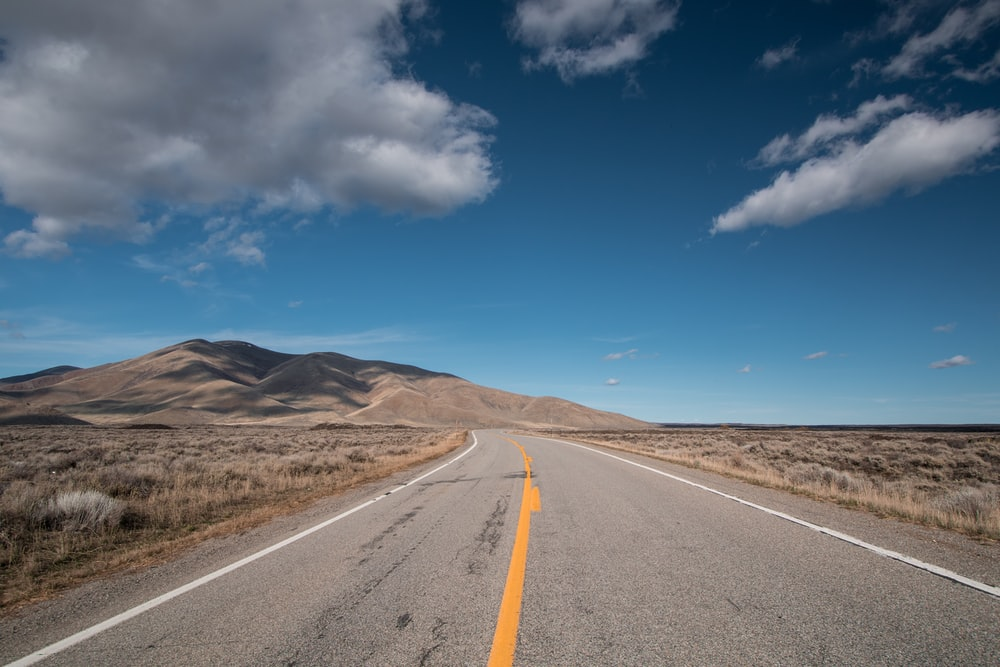selective focus photo of road under blue sky