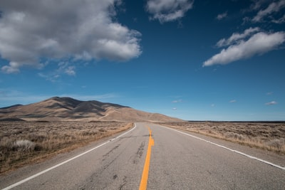 selective focus photo of road under blue sky idaho zoom background