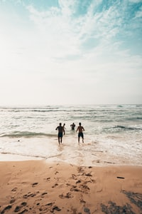 men running toward beach