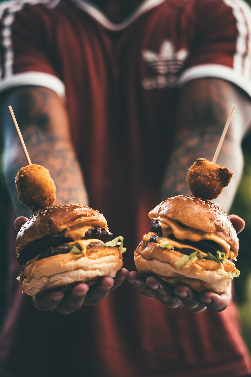 person holding two cheese hamburgers