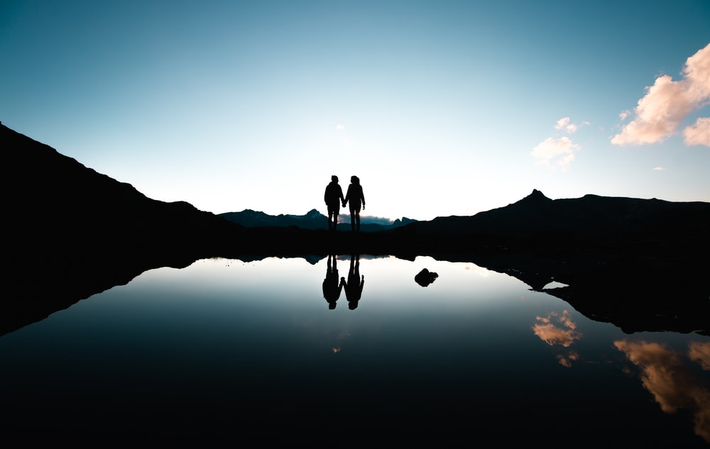 silhouette of people holding hands in front of body of water under blue sky