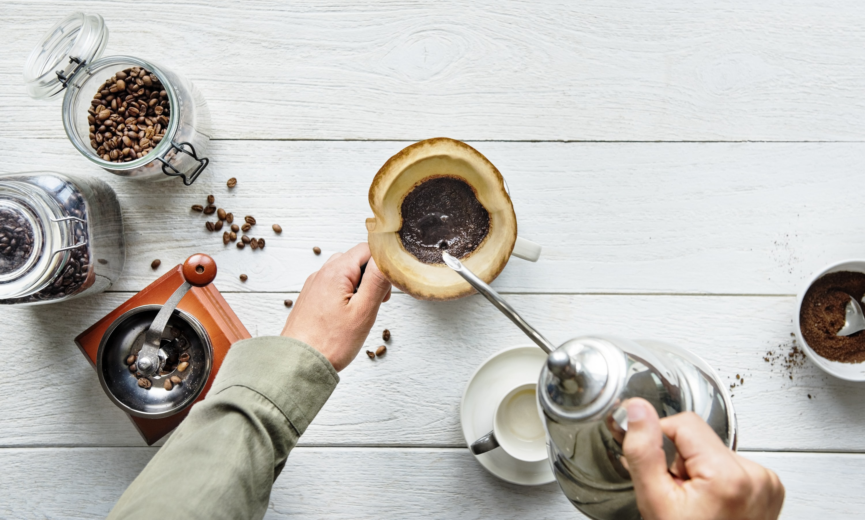 person pouring liquid in brown mug