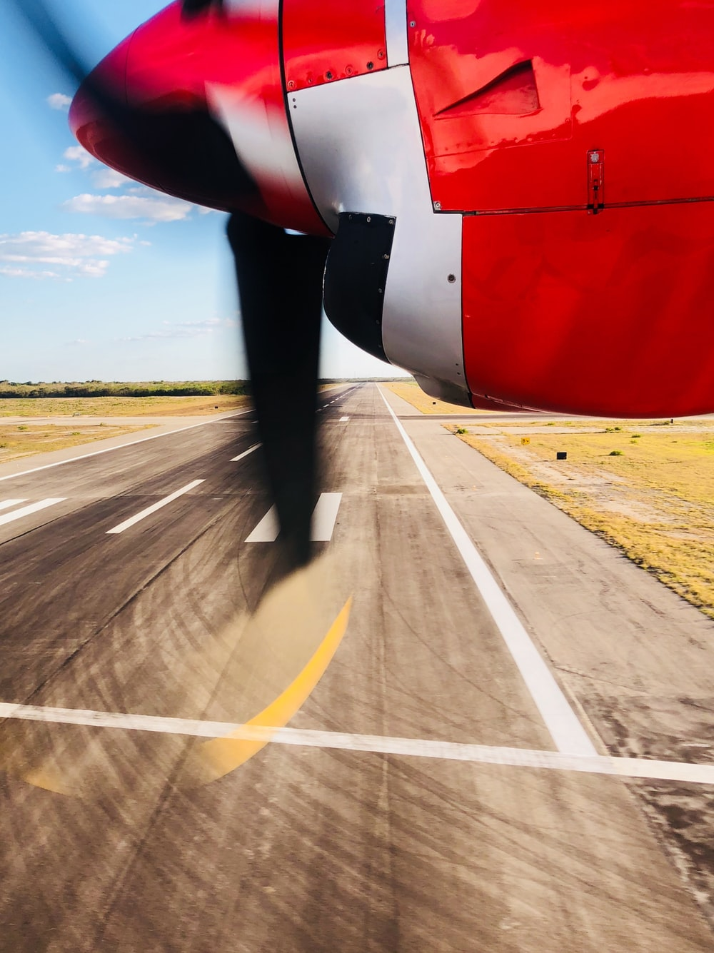 close-up photography white and red plane above runway