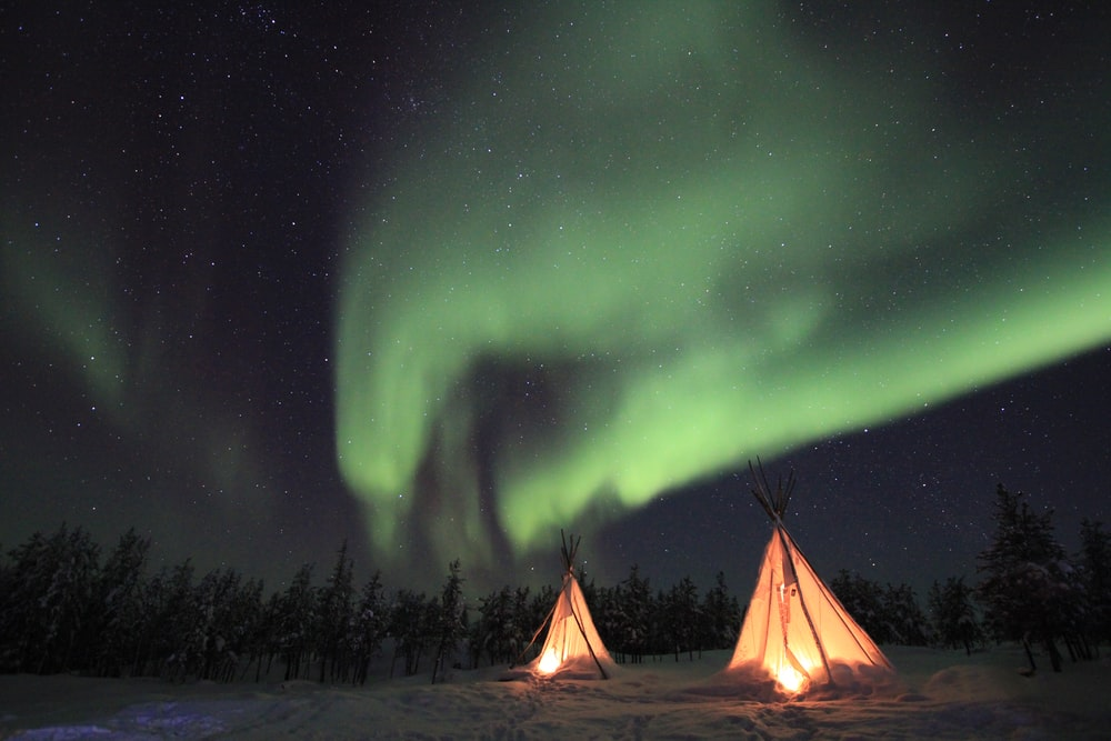 lighted tipi tent under green Northern lights