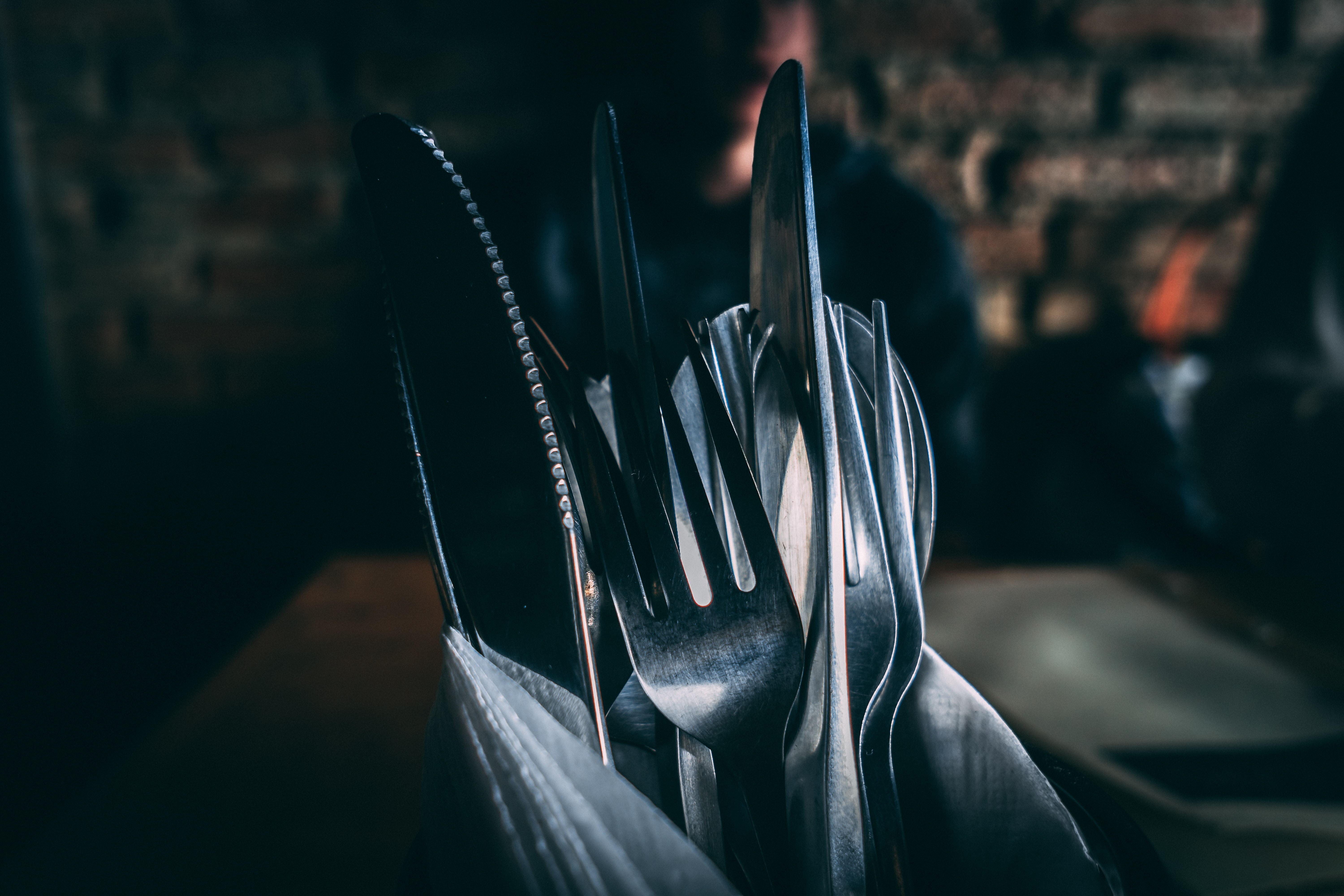 focus photography of silver utensils on container