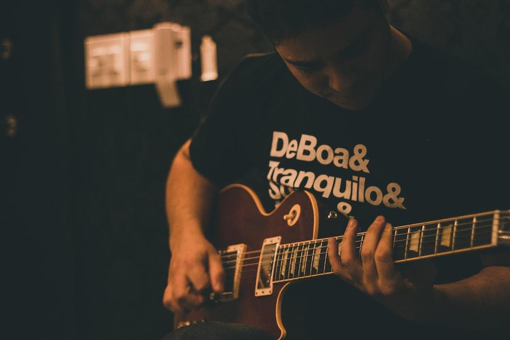 man playing brown guitar