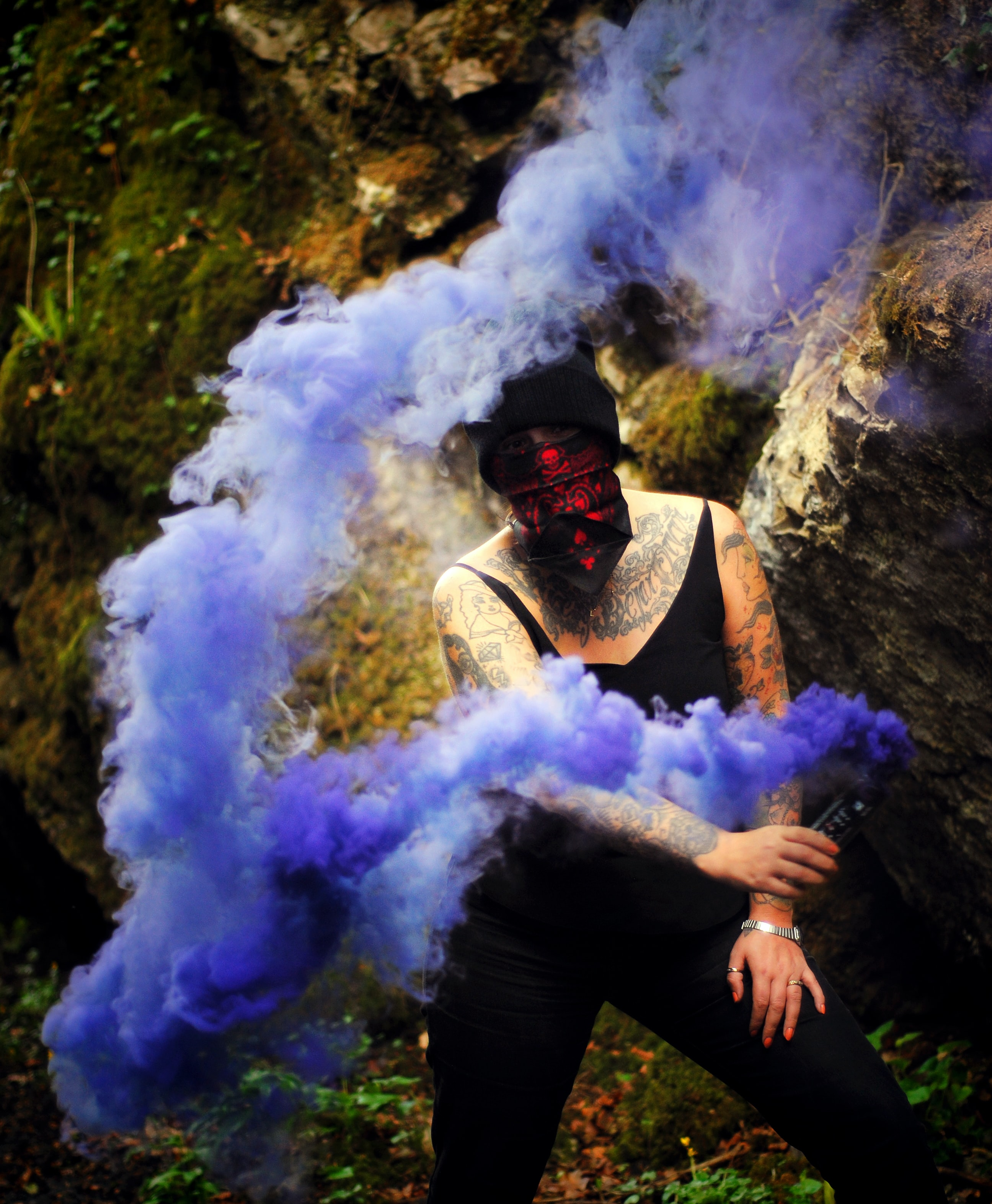 woman standing beside rock while holding smoke flare