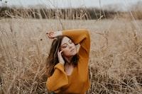 woman raisin hand up on brown field
