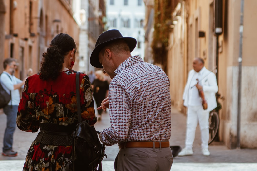 This is a couple understanding where to go in Rome. She has a beautiful flower dress, he wears a vintage hat and in the background there is a man that will play his violin in all white suit. Everything talks about a beautiful day, Rome and Piazza di Spagna.