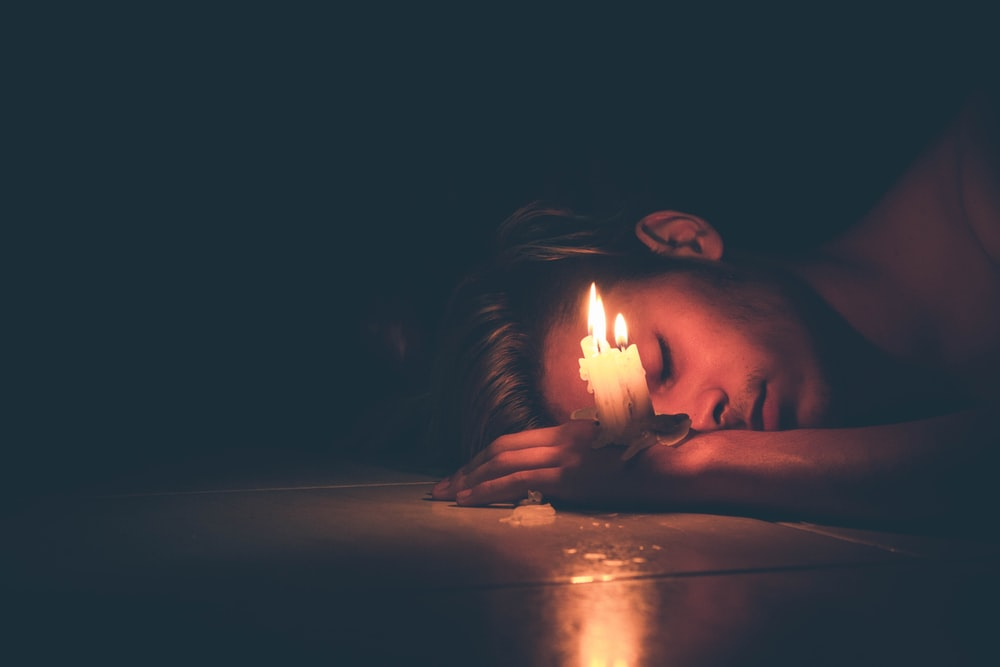 lighted candles on man's hand lying on the floor