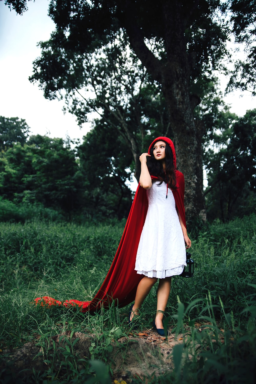 woman cosplaying little riding hood near tree