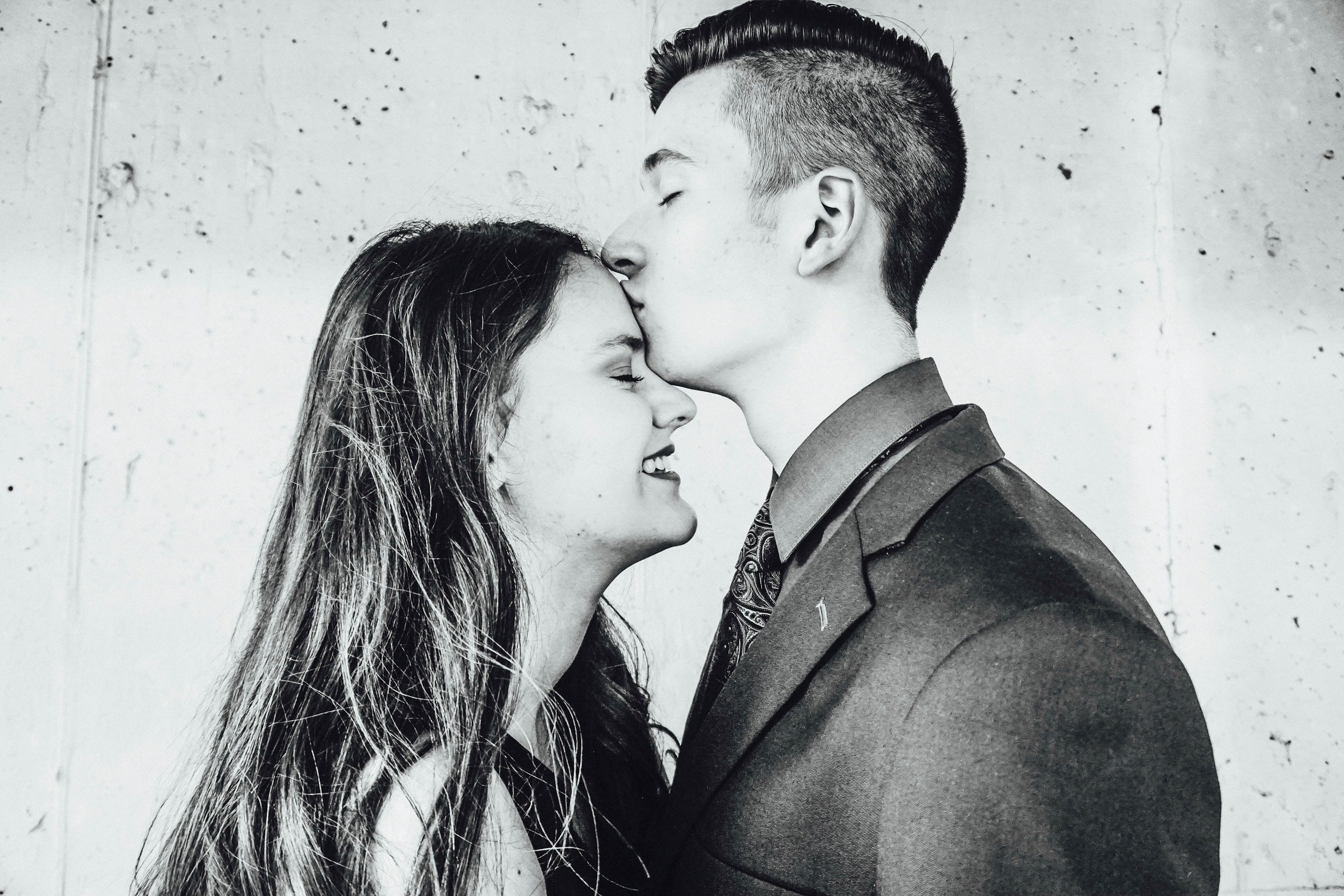 grayscale photo of man kissing woman