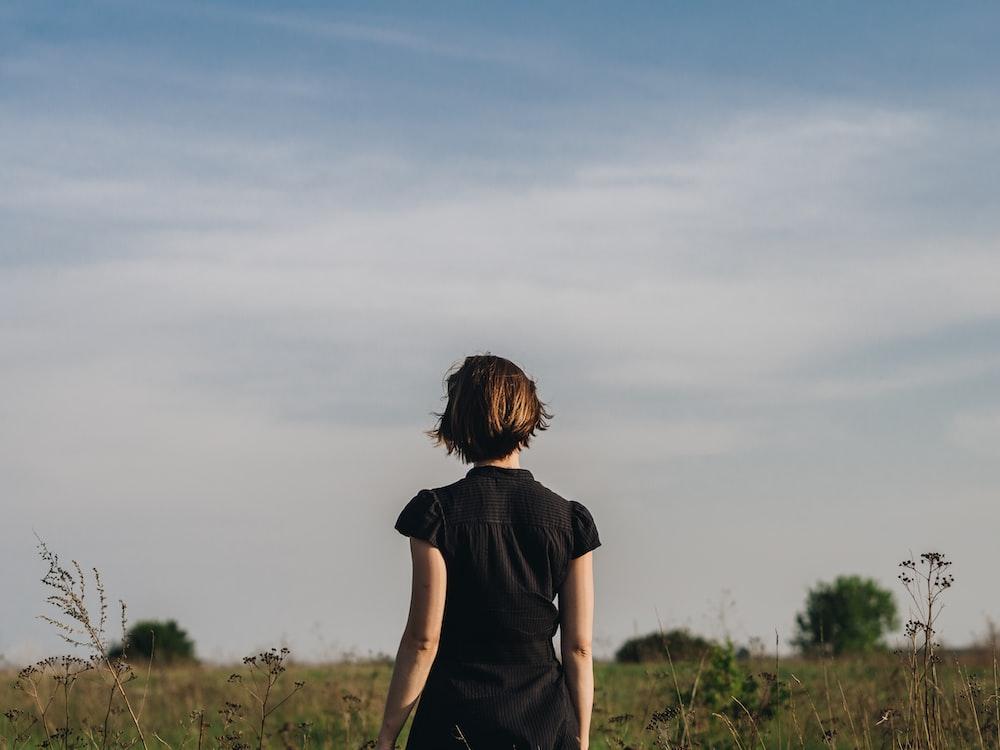 woman in black shirt standing in grass field